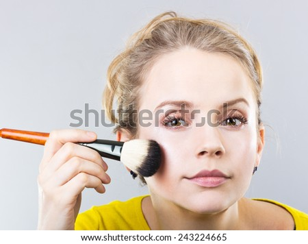 beautiful blonde girl does makeup. Girl apply cosmetic powder. Portrait of a girl. - stock photo