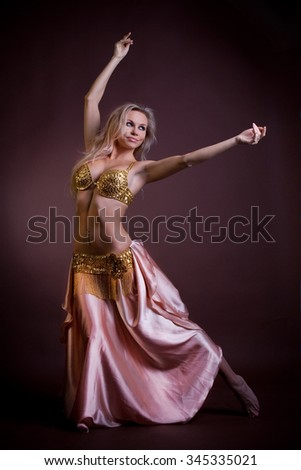 Beautiful blonde girl dressed as a choreographer for oriental belly dancing in the studio posing on a brown background, dancing