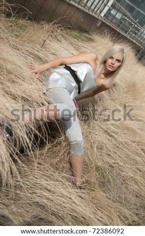 Beautiful blonde girl dressed in a futuristic style is sitting on dry grass