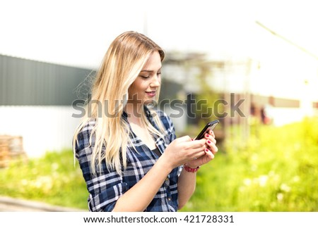 Beautiful blonde girl dressed in checkered shirt typing message on smartphone - stock photo