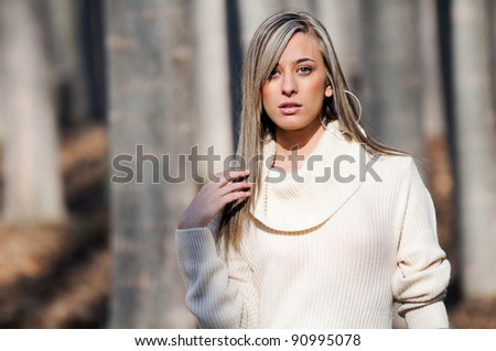 Beautiful blonde girl, dressed with a beige dress, standing in a poplar forest