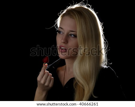 Beautiful blonde girl eating strawberry isolated on black