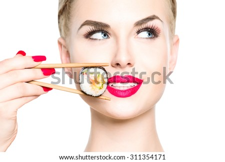 Beautiful blonde girl eating sushi close-up isolated on white. Smiled woman with perfect make up holding Sushi roll with chopsticks. Healthy Japanese food. Diet concept - stock photo