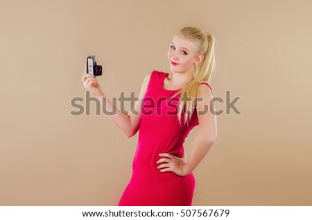 Beautiful blonde girl in a bright dress photographed herself on the old-style camera