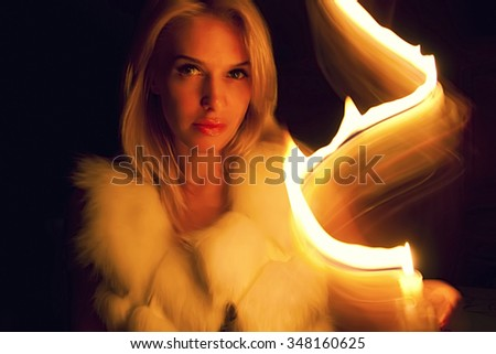 Beautiful blonde girl in a fur vest in the darkness, light a candle herself, from a candle left a fiery trail - stock photo