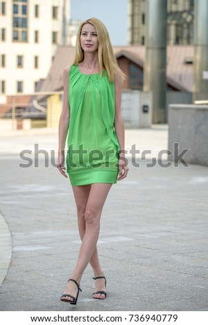 Beautiful blonde girl in a green short summer dress on the streets of the city