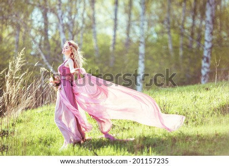 Beautiful blonde girl in a pink dress on a long evolving nature background  - stock photo