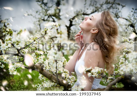 beautiful blonde girl in a white flowering garden - stock photo