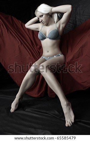 Beautiful blonde girl in blue lingerie posing on red background. - stock photo