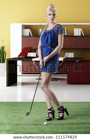 beautiful blonde girl in full lenght plays golf with blue short dress and hig shoes, takes golf-club with both hands and looks in to the lens - stock photo