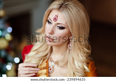 beautiful blonde girl in Indian red saree around the Christmas tree, close up