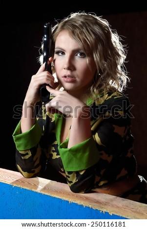 Beautiful blonde girl in military khaki shirt with gun - stock photo