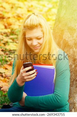 Beautiful blonde girl in nature with cell phone in park - stock photo