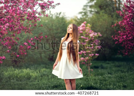 Beautiful blonde girl in pink peach and sakura garden. Beautiful girl outdoors spring portrait, young woman with flowers in green park spring concept - stock photo