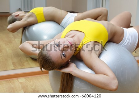 Beautiful blonde girl in shorts do exercise on big ball in fitness gym - stock photo