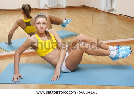 Beautiful blonde girl in shorts do exercise on floor mat in fitness gym - stock photo