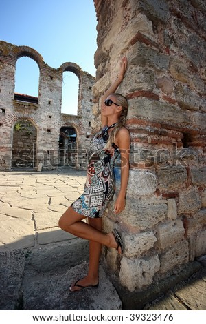 Beautiful blonde girl in sunglasses at the column in old town