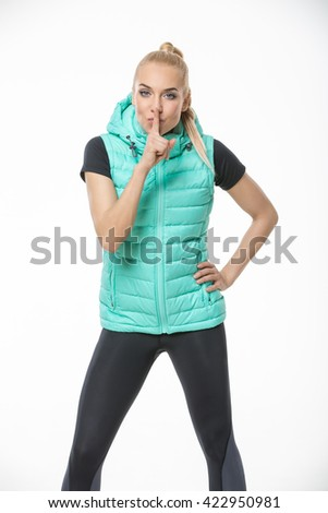 Beautiful blonde girl in the sportswear stands on the white background in the studio. She wears black-gray pants, black t-shirt and mint vest. She holds her left hand on her hip. She presses her right - stock photo