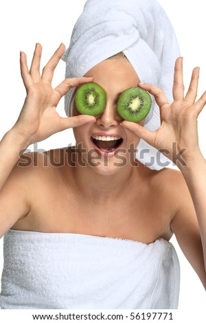 Beautiful blonde girl in towel takes kiwi before her eyes on white - stock photo