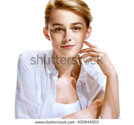 Beautiful blonde girl in white shirt on white background. Close-up of an attractive girl of European appearance. Youth and skin care concept - stock photo