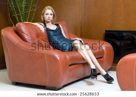 Beautiful blonde girl is sitting on the sofa in office - stock photo