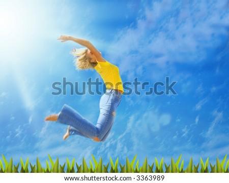 Beautiful blonde girl jumps over green grass - stock photo