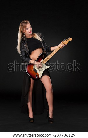 Beautiful blonde girl playing guitar in rock style on a black background - stock photo