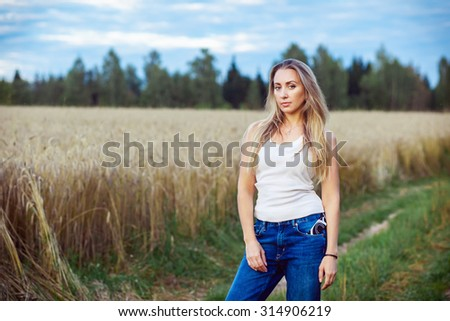 Beautiful blonde girl posing in a field at sunset - stock photo