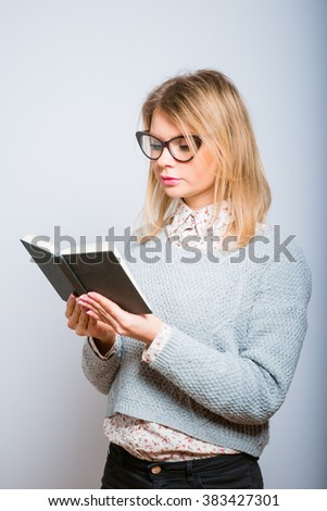 beautiful blonde girl reading a notebook, isolated on a gray background - stock photo