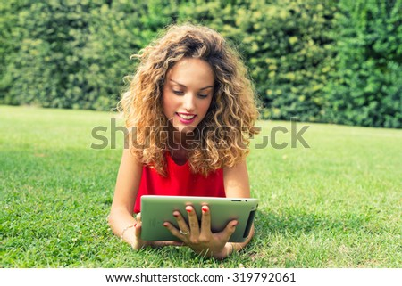 Beautiful blonde girl reading tablet on the grass.