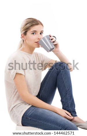Beautiful blonde girl sitting and drinking coffee, over a white background - stock photo