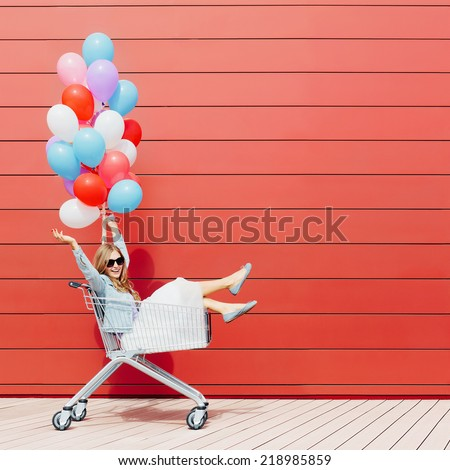 Beautiful blonde girl sitting in shopping cart, color balloons in her one hand. Smiling, laughing. Sunny day, outside - stock photo
