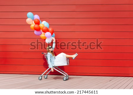 beautiful blonde girl sitting in shopping cart, holding color balloons in her hand. Sunny day, outside - stock photo