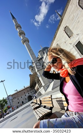 Beautiful blonde girl sitting on the bench at the islamic mosque