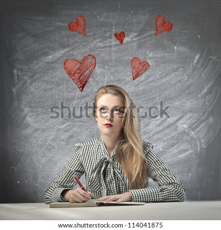 Beautiful blonde girl thinking love while writing
