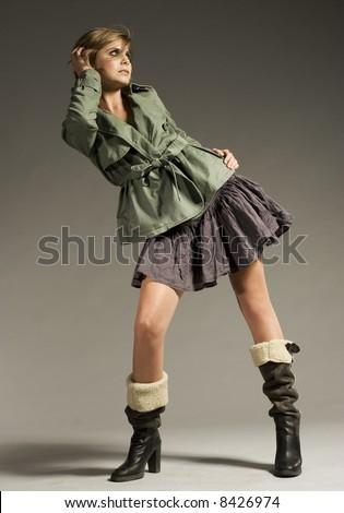 beautiful blonde girl wearing green coat and mini skirt on grey background - stock photo