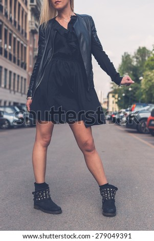 Beautiful blonde girl with black minidress and leather jacket posing in the city streets