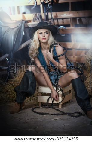 Beautiful blonde girl with country look, indoors shot in stable, rustic style. Attractive woman with black cowboy hat and denim shorts, American country style farmer with barn harness in background - stock photo