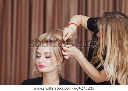 Beautiful blonde girl with long hair doing an professional evening hairdress in a beauty salon