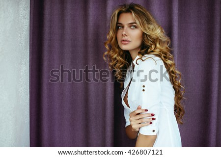 Beautiful blonde girl with long hair. With hair and makeup, posing in the morning in an apartment on the background of purple curtains in a white shirt. The light from the window, soft focus - stock photo