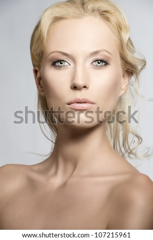 beautiful blonde girl with nudes shoulders and natural makeup, she is in front of the camera and looks in to the lens with sensal expression - stock photo