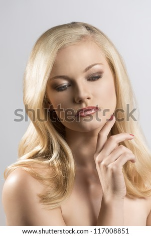 beautiful blonde girl with smooth hair and naked shoulders, she looks down and has the right hand near the chin - stock photo
