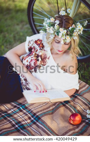 Beautiful blonde girl with sunflowers. Picnic in the park in the summer at sunset. Lovely girl on a bicycle in a retro style.