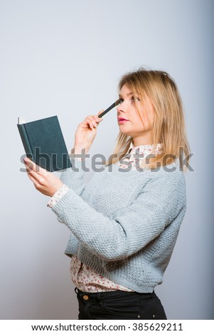 beautiful blonde girl writes down the idea of a notebook, isolated on a gray background
