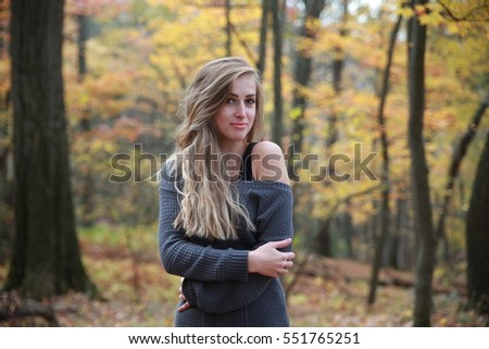 Beautiful blonde gold woman feeling cold and smiling with hands near her mouth while standing at autumn or spring forest outdoors wearing red jersey, Walking in a park, close portrait beautiful bokeh