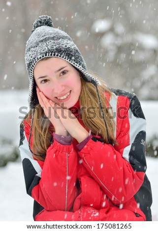 Beautiful blonde hair girl with black cap in winter - stock photo