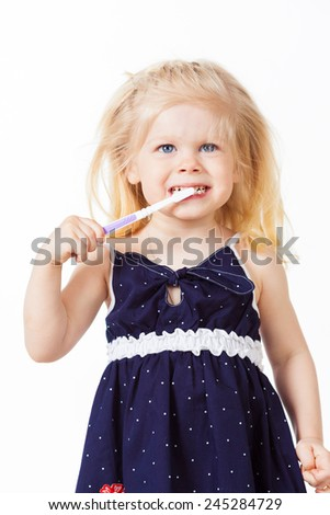 Beautiful blonde haired baby girl brushes her teeth on white background - stock photo
