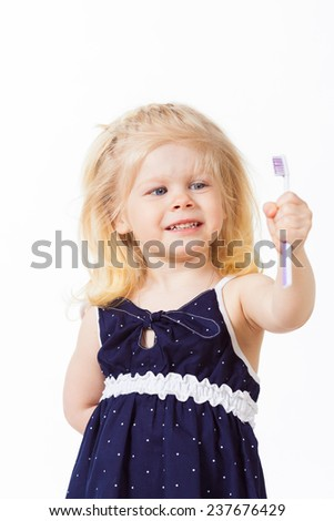 Beautiful blonde haired girl looking at toothbrush in her hand - stock photo
