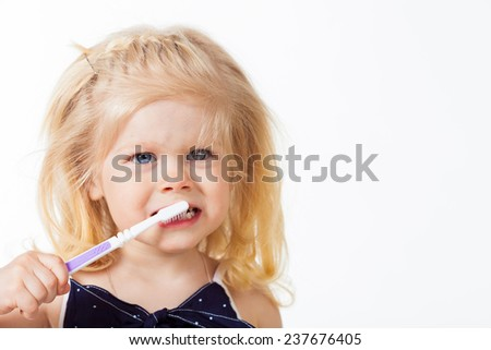 Beautiful blonde haired girl with toothbrush in her hand on white - stock photo