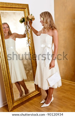 Beautiful blonde haired woman in white bridal dress - stock photo